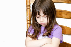 Pouting Child. Small girl sitting on ladder-back chair pouting Royalty Free Stock Photos