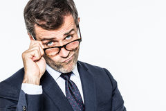 Pouting far-sighted elegant businessman moving eyeglasses down for disappointment Stock Photography