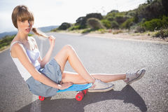 Pouting funky blonde sitting on her skateboard Stock Photos