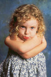 Pouting Little Girl. A curly-haired little girl strikes a pouty pose in the studio Stock Photos