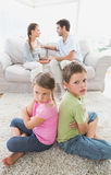 Pouting siblings sitting back to back while parents are arguing Stock Photos