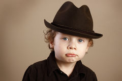 Pouting Toddler with Fedora. A closeup of a cute toddler with a pout, curly blond ringlets and blue eyes wearing a stingy brim fedora. Shallow depth of field and stock photo