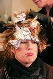 Pouting woman having hair colored. Beautiful woman having hair colored with foil in a salon Royalty Free Stock Photos