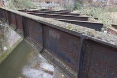 Poutres corrodées à travers la rivière urbaine Photo stock