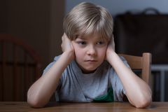 Pouty boy covering ears Stock Images