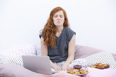 Pouty woman sitting on bed Stock Images