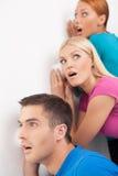 Pouvez-vous entendre cela ? Les trois jeunes écoutant clandestinement près du wal Photo stock