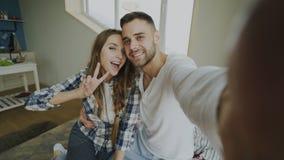 POV年轻人微笑和美好的夫妇采取在智能手机照相机的selfie画象并且亲吻,当坐在时的床 免版税图库摄影