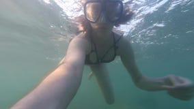 POV年轻逗人喜爱的棕色毛发的妇女水下与看对行动照相机的游泳面具,潜水,不用水肺在海 股票录像