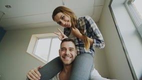 POV愉快微笑和美好的夫妇采取在智能手机照相机的selfie画象,当女孩坐人` s脖子在时 免版税库存照片