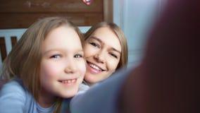 POV снял околпачивать усмехаясь ребенка и счастливой милой женщины целуя и делать selfie видеоматериал