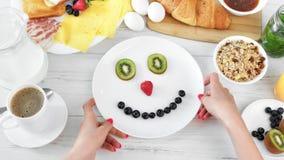 POV βλαστάησε το θηλυκό χέρι που έχει το παιχνίδι διασκέδασης με το πρόσωπο μούρων φρούτων χαμόγελου στη τοπ άποψη πιάτων φιλμ μικρού μήκους