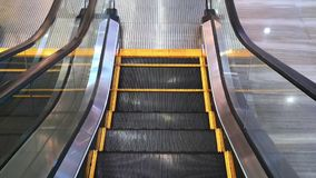 POV ενός προσώπου σε μια κυλιόμενη σκάλα που κινείται κάτω από τα σκαλοπάτια - κενή σύγχρονη κυλιόμενη σκάλα με τις κίτρινες γραμ απόθεμα βίντεο
