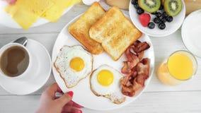 POV πυροβόλησε το θηλυκό χέρι προσθέτοντας το τηγανισμένο αυγό στο πιάτο με τη φρέσκια νόστιμη τοπ άποψη τροφίμων μπέϊκον και φρυ απόθεμα βίντεο