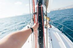 POV της εκμετάλλευσης χεριών επάνω στον ιστό sailboat στοκ εικόνα