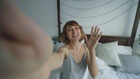 POV жизнерадостной женщины имея онлайн видео- болтовню при друзья используя камеру smartphone пока сидящ на кровати дома Стоковые Изображения