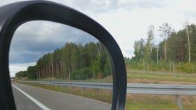 POV пассажира автомобиля, ландшафт обочины отразил в зеркале взгляда со стороны, управляя сток-видео