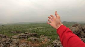 POV, пеший туризм человека туристский на холме утеса смотря вокруг с поднятой рукой видеоматериал