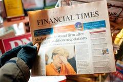 POV av bärande handskar för manlig hand som rymmer The Financial Times nyheterna Royaltyfri Fotografi