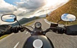 POV av den hållande styrningstången för motorbiker, ridning i fjällängar Fotografering för Bildbyråer