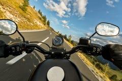 POV av den hållande styrningstången för motorbiker, ridning i fjällängar Arkivfoton