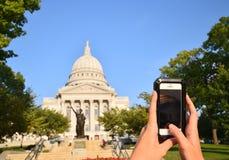 Pov av kvinnan som tar fotografiet med en smartphone av huvudbyggnaden i Madison, Wisconsin arkivbild