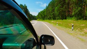POV: Car is moving across the Wood in sunny day on a road Stock Photos