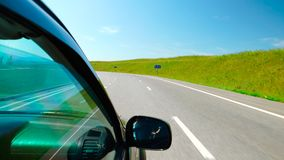 POV: Car is moving along the green hills on a highway Stock Photo