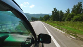 POV: Car is moving along the trees and mountains on a highway in Altay, Russia. POV: Car is moving along the trees and mountains on a highway in Altay Russia stock footage