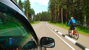 POV: Car is moving on curving road near a bicycle Royalty Free Stock Image