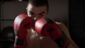 POV close up of an athletic muscular kickboxer looking into the camera while he shadow boxes in slow motion -. POV close up of an athletic muscular kickboxer stock video footage