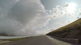 Pov of countryside road with hills and cloudy sky in background seen from drive vehicle traveling  -. Pov of countryside road with hills and cloudy sky in stock video