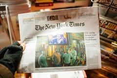 POV das luvas vestindo da mão masculina que guardam New York Times Mugab fotos de stock