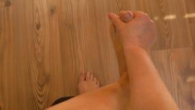 POV de la mujer madura paciente con dolores reumáticos en las piernas que se sientan en cama y que frotan su tobillo y pie metrajes