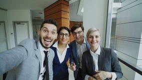 POV del equipo feliz del negocio que tiene charla video en línea usando cámara del smartphone y que habla con su colega en modern