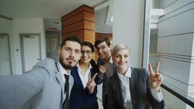 POV del equipo feliz del negocio que toma el retrato del selfie en cámara del smartphone y que presenta para la foto del grupo du