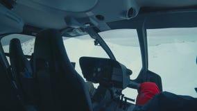 POV del interior de un helicóptero que vuela sobre las montañas de la nieve almacen de metraje de vídeo