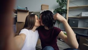 POV del marido y de la esposa que toman el selfie con las nuevas llaves planas que se besan y que presentan almacen de metraje de vídeo