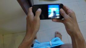POV dell'uomo che si siede sulle foto di sorveglianza della toilette sullo Smart Phone delle cellule mentre porta aperta della ra stock footage