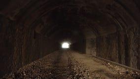 Pov, der nach innen vom alten dunklen langen verlassenen Tunnel mit hellem Licht am Ende geht stock video