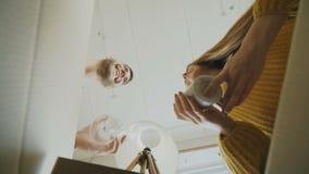 POV des glücklichen Paars küssend beim Öffnen der Pappschachtel nach Verlegung und Schauen inner und Nehmen von Sachen in neuem stock video