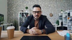 POV des gut aussehenden Mannes sprechend gestikulierend, Kamera unter Verwendung des Computers betrachtend bei der Arbeit stock video footage