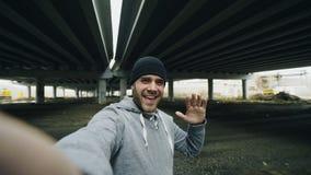 POV des sportiven Mannes, der Videochat auf Smartphone mit Freunden nach Training am städtischen Standort draußen im Winter hat stockfoto