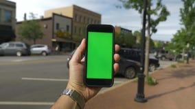 POV die in Kleine Stad met het Groene Scherm Smartphone draaien stock footage