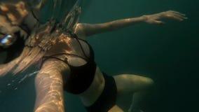 POV die van jonge bruin-haired vrouw onderwater met zwemmend masker die aan actiecamera kijken, zonder aqualong in overzees duike stock footage