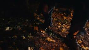 POV die van slachtoffer van gekke maniak in donker bos, seriemoordenaar met knuppel ontsnappen stock videobeelden