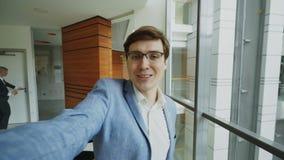 POV do homem de negócios novo no terno que tem o bate-papo video em linha usando a câmera do smartphone e falando a seus colegas