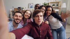 POV dos jovens alegres que tomam o selfie com caras engraçadas e gestos de mão filme