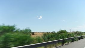 POV driving in countryside from car window past fields, trees and windmills in Larnaca, Cyprus stock video footage