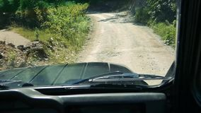 POV driving jeep on winging rough path between green plants. Asphalt and dirt roads. Sunny summer day. Somewhere in Russia stock video footage